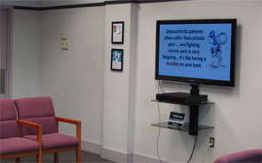 The TV in the reception area plays the physician's videos on YouTube.