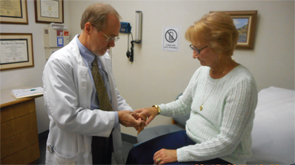 Dr. Truslow performs a routine examination of the hand of a patient with rheumatoid arthritis.