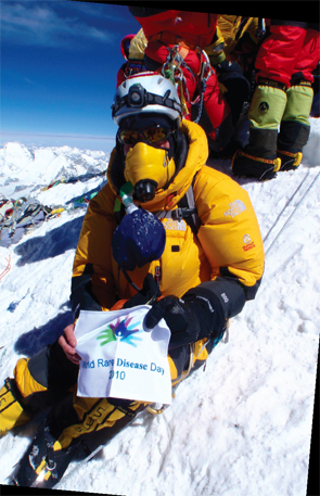 On the summit of Mt.  Everest, Ms. Abbott displays a banner for the National Organization of Rare Disorders.