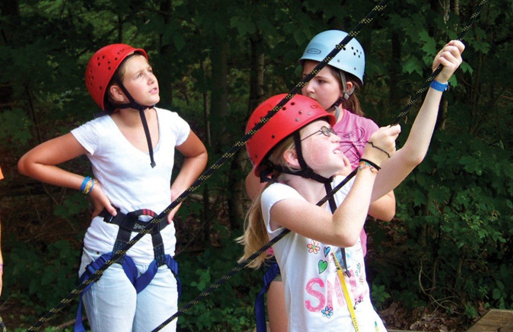 Campers check the ropes before beginning their next challenge.