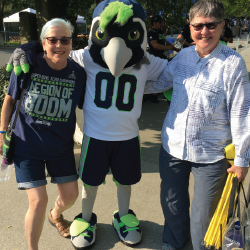 Rosemary Brechtelsbauer (left) and her wife, Cheryl (right) enjoying life at a Seattle Seahawks football game with the mascot.