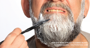 Hair dye being applied to a man's beard.
