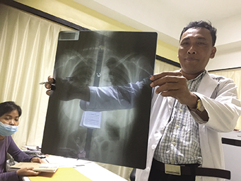Dr. Rithya, who manages the rheumatology clinic, examines a patient's X-ray.