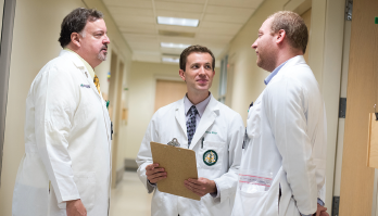 Dr. Bridges converses with colleagues at UAB Medicine.