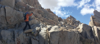 Dr. Criswell hikes a narrow rocky ledge close to the top of Mt. Whitney.