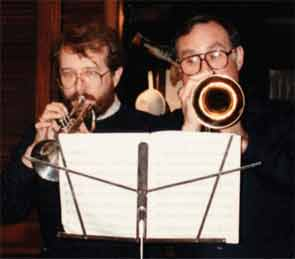 Drs. Scofield and Reichlin perform on their trumpets at a holiday gathering.