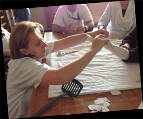 Therapist in Bitola fabricating a resting hand orthosis for a person with RA.