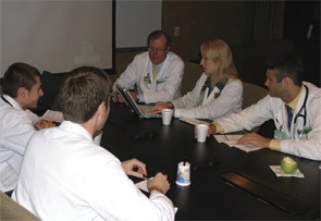 Dr. Sergent (back center) sharing knowledge with some young physicians.