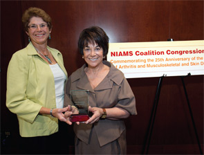Janet Stearns Wyatt, PhD, RN, CRNP (at left), presents Representative Anna Eshoo (D-CA) with a 2011 NIAMS Coalition Congressional Champion award.