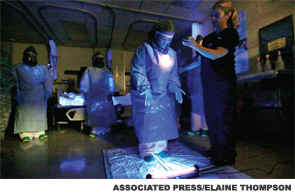 During a training demonstration at Madigan Army Medical Center on Joint Base Lewis McChord, near Tacoma, Wash., a medical worker wearing personal protective equipment is illuminated with a black light to look for traces of ultraviolet-responsive liquid that represents fluids, which could transmit the Ebola virus.